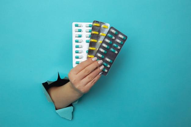 Kobieta ręka dając blister tabletek przez otwór rozdarty w niebieskiej ścianie papieru. opieka zdrowotna i przełom farmaceutyczny