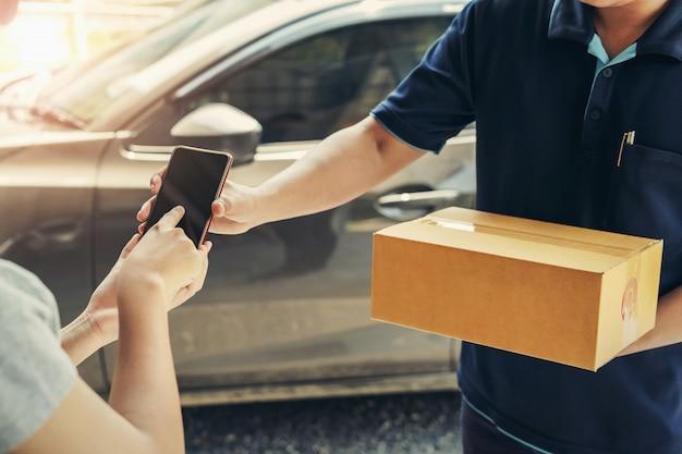 Kobieta ręka dołączając podpis w telefonie komórkowym do odbioru paczki