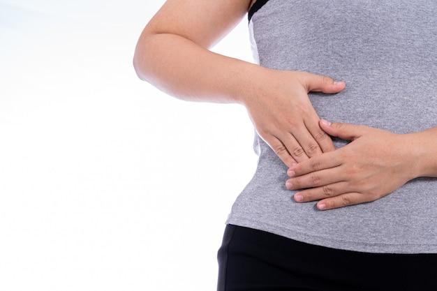 Kobieta ręką dotykając pozycji żołądka, talii lub wątroby na białym tle.