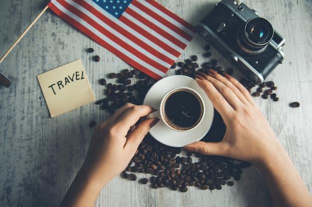 Kobieta ręka kawa z koncepcją podróży na stole