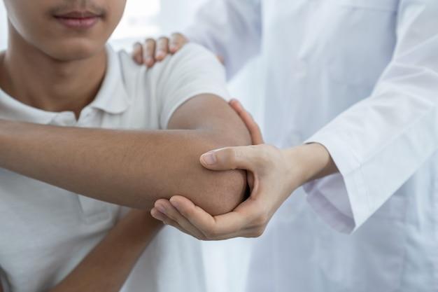 Kobieta ręka lekarza robi fizjoterapię poprzez wyciągnięcie ramienia pacjenta płci męskiej.