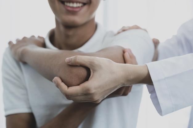 Kobieta ręka lekarza robi fizjoterapii poprzez wyciągnięcie ramienia pacjenta płci męskiej.