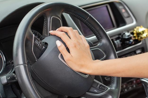 Kobieta ręka na kierownicy i trąbi róg prawą ręką.