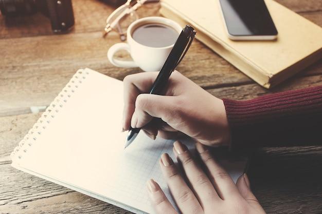 Kobieta ręka piórem pisanie na notatniku na stole roboczym