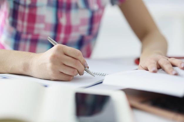 Kobieta ręka pisania długopisem w zbliżeniu notatnika