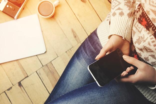 Kobieta ręka telefon kawa notatnik i długopis na podłodze