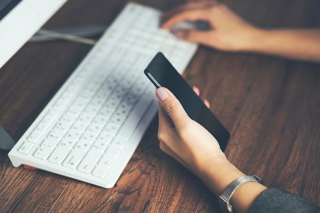 Kobieta ręka telefon z działającą klawiaturą na stole