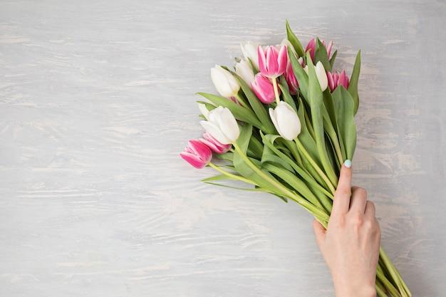 Kobieta ręka trzyma białe i różowe kwiaty tulipanów na lekkiej drewnianej ścianie. flat lay, top view minimalna świąteczna koncepcja wiosennego kwiatu z miejscem na kopię.