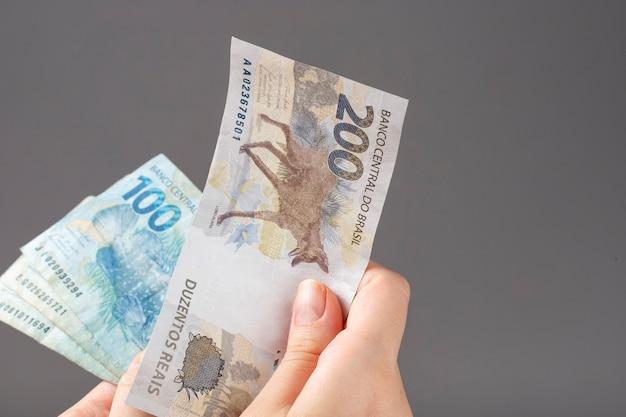 Kobieta ręka trzyma brazylijskie banknoty