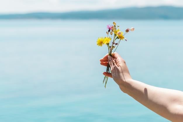 Kobieta ręka trzyma bukiet żółtych kwiatów