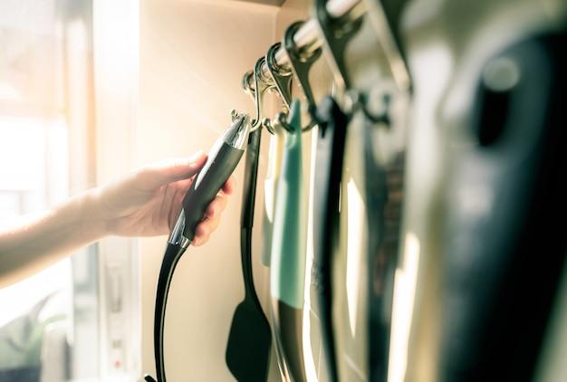 Kobieta ręka trzyma czarny plastikowy uchwyt szpatułki. kobieta gotowania potraw w kuchni mieszkania. zestaw przyborów kuchennych zawieszony na wieszaku ściennym ze stali nierdzewnej. nowoczesna i współczesna kuchnia.