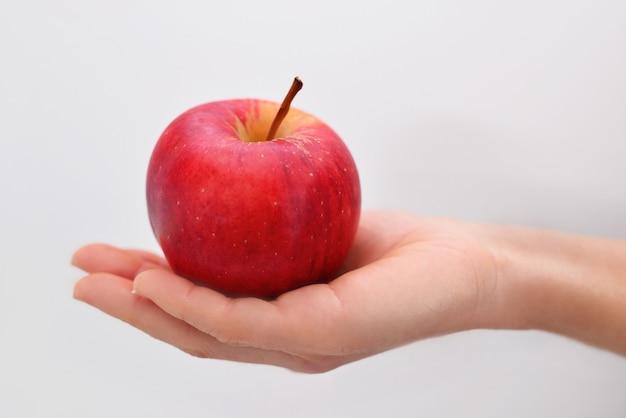 Kobieta ręka trzyma czerwone jabłko na białym tle na białej ścianie.