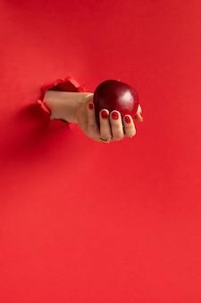 Kobieta ręka trzyma czerwone jabłko przez otwór w czerwonej ścianie papieru