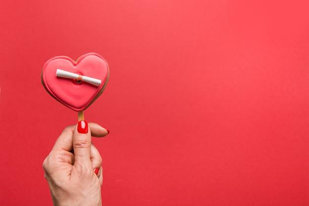 Kobieta ręka trzyma czerwone przeszklone ciasteczka w kształcie serca