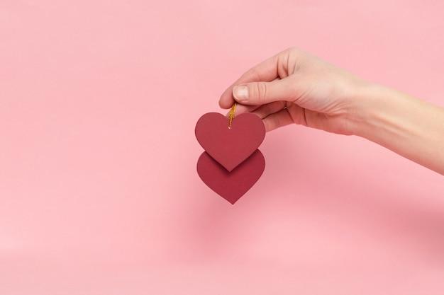 Kobieta ręka trzyma czerwone serca dekoracje walentynkowe, prezent. miłość, romantyczna koncepcja z miejsca na kopię na różowym tle