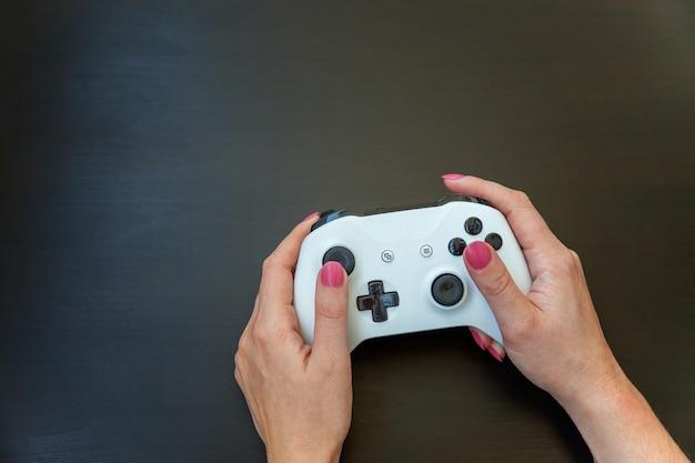 Kobieta ręka trzyma gamepad biały joystick, konsola do gier na białym tle na czarnym tle