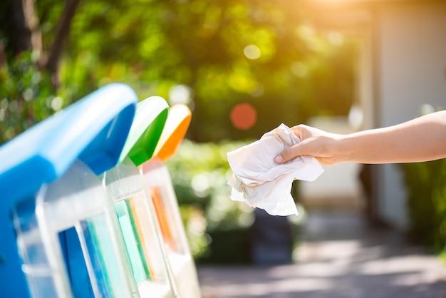 Kobieta ręka trzyma i wkłada zagadnienie papierowego odpady w śmieci kosz.