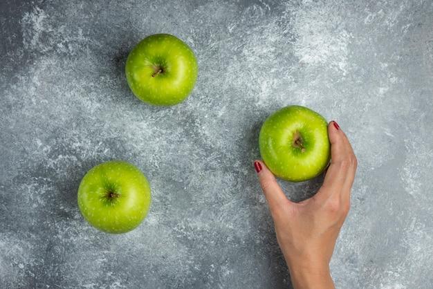 Kobieta ręka trzyma jedno jabłko z trzech na marmurze.