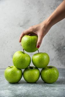 Kobieta ręka trzyma jedno jabłko z wielu.