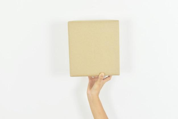Kobieta ręka trzyma karton na białym tle z miejsca na kopię