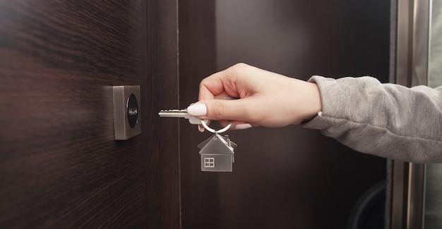 Kobieta ręka trzyma klucz do domu w domu.