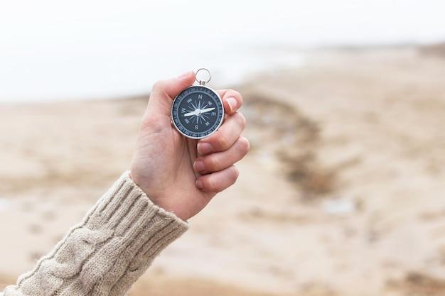 Kobieta ręka trzyma kompas przed niewyraźne wybrzeże, plaża. sprzęt turystyczny. nawigacja w podróży. znajdź drogę i miejsce docelowe. zachód czy wschód