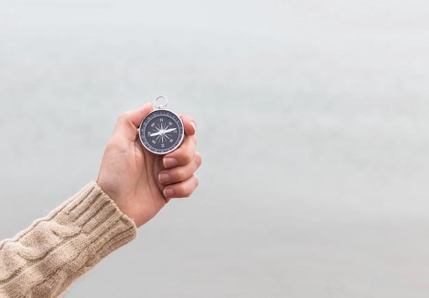Kobieta ręka trzyma kompas przed światłem niewyraźne morze. sprzęt turystyczny. nawigacja w podróży. znajdź drogę i miejsce docelowe. zachód czy wschód