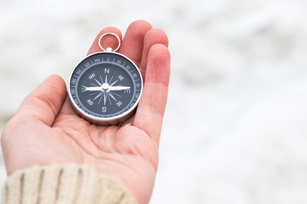 Kobieta ręka trzyma kompas przed światłem niewyraźne tło. sprzęt turystyczny. nawigacja w podróży. znajdź drogę i miejsce docelowe. zachód czy wschód
