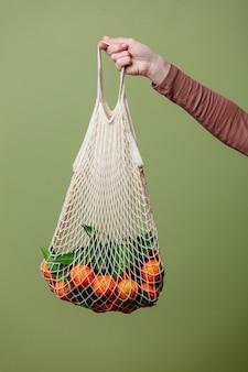 Kobieta ręka trzyma mandarynki w worek strunowy