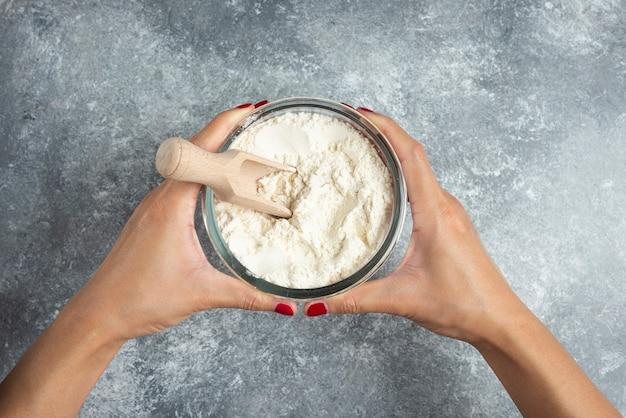 Kobieta ręka trzyma miskę mąki na marmurze.