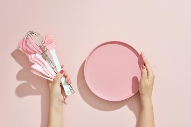 Kobieta ręka trzyma naczynia kuchenne na różowo. narzędzia do pieczenia