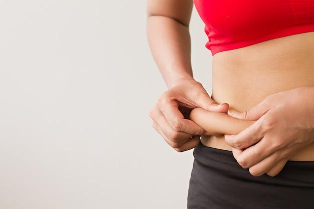 Kobieta ręka trzyma nadmiernego tłuszczu z brzucha, problem otyłości portretowane przez tłuszcz na brzuchu kobiety