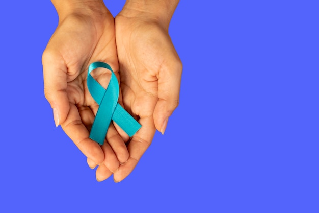 Kobieta ręka trzyma niebieską wstążkę, kampania uświadamiająca na temat raka prostaty. kobieta zaniepokojona stanem zdrowia mężczyzny. niebieski listopad.