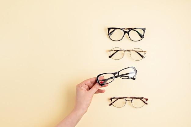 Kobieta ręka trzyma okulary. sklep optyczny, dobór okularów, badanie wzroku, badanie wzroku u optyka, koncepcja akcesoriów modowych. widok z góry, płaski układ