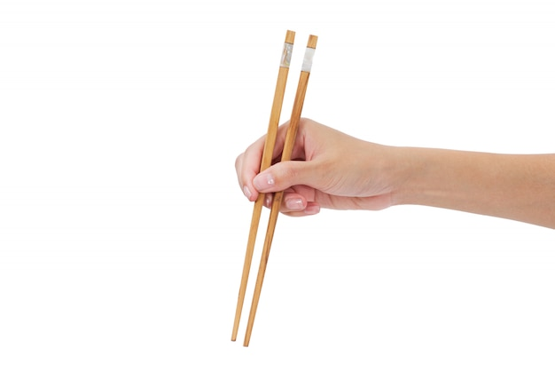 Kobieta ręka trzyma pałeczki na białym tle