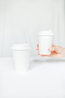 Kobieta ręka trzyma papierowy kubek kawy