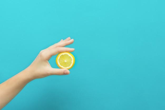 Kobieta ręka trzyma plasterek owoców cytryny na niebieskim tle z miejsca na kopię.