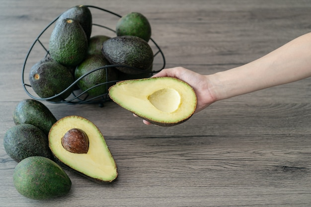 Kobieta ręka trzyma pokroić pół, pokrojone świeże zielone awokado na brązowym drewnianym stole. owoce koncepcja zdrowej żywności.
