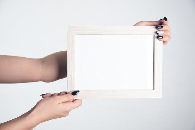 Kobieta ręka trzyma pustą ramkę na zdjęcia.