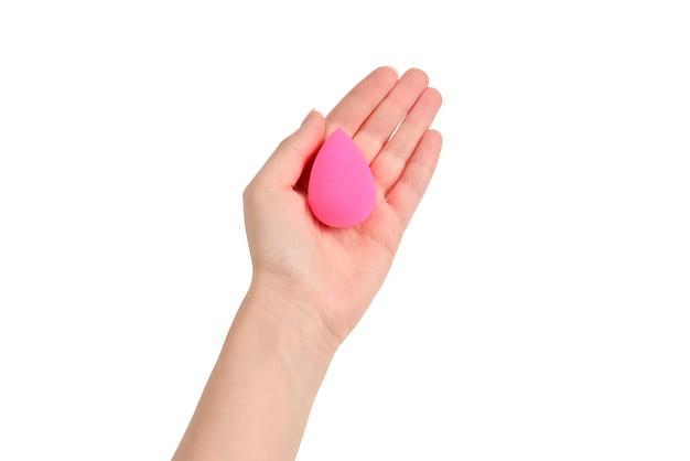 Kobieta ręka trzyma różową gąbkę piękności na białym tle.