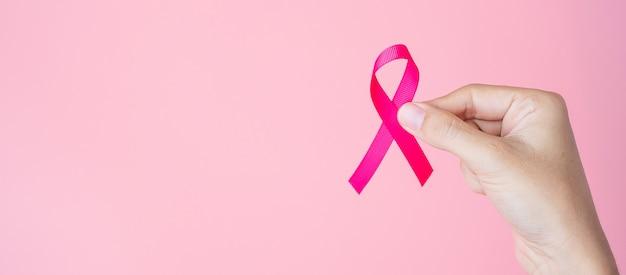 Kobieta ręka trzyma różową wstążkę