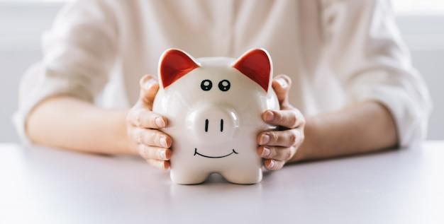 Kobieta ręka trzyma skarbonkę na stole, oszczędza pieniądze i inwestycje finansowe