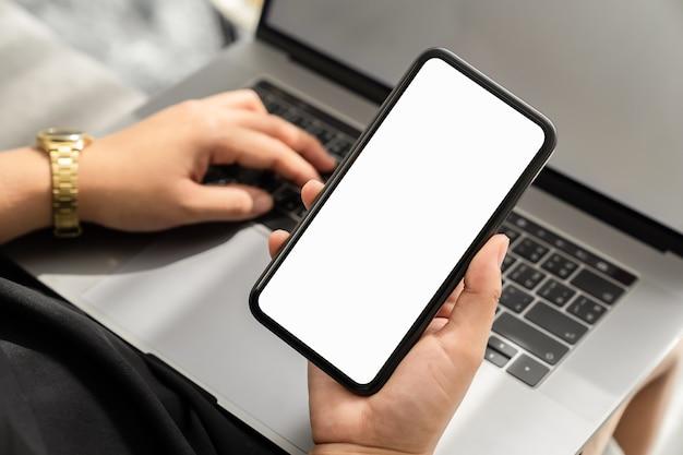 Kobieta ręka trzyma smartfon z pustym ekranem miejsca na twoje ogłoszenie. laptop na stole.