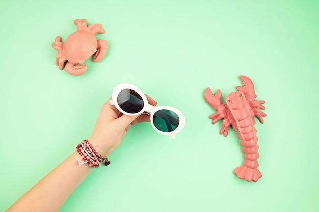 Kobieta ręka trzyma stylowe okulary przeciwsłoneczne. letnie wakacje, wakacje, koncepcja stylu mody na lato. widok z góry. leżał na płasko