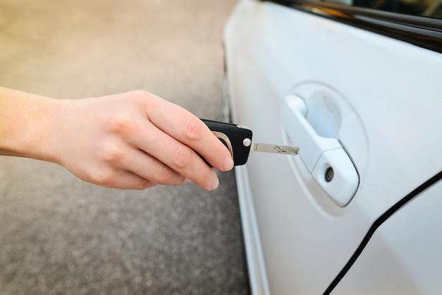 Kobieta ręka trzyma systemy alarmowe zdalnego sterowania samochodu