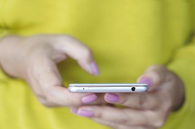 Kobieta ręka trzyma telefon komórkowy łączący z internetem