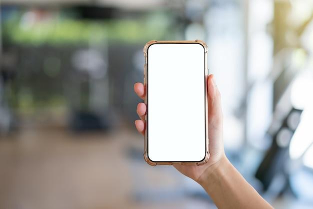 Kobieta ręka trzyma telefon komórkowy z makietą pusty biały ekran