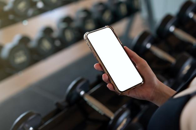 Kobieta ręka trzyma telefon komórkowy z pustym białym ekranem w siłowni.