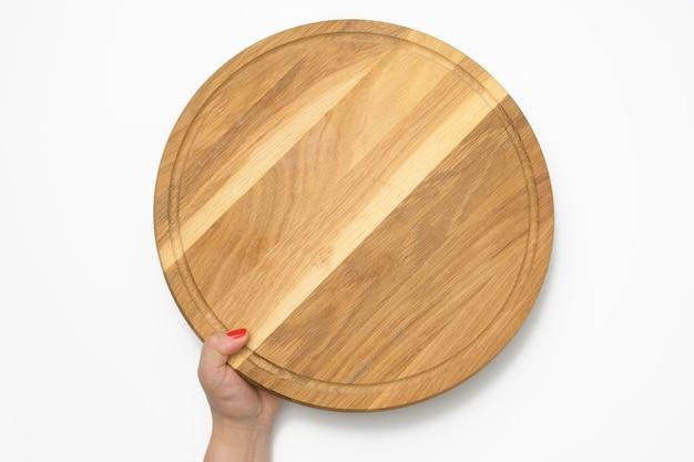 Kobieta ręka trzyma w ręku pustą okrągłą drewnianą deskę do pizzy, część ciała na białym tle
