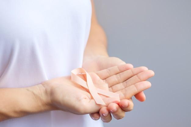 Kobieta ręka trzyma wstążkę brzoskwini dla miesiąca świadomości raka macicy września. koncepcja opieki zdrowotnej i światowego dnia raka
